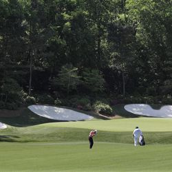 Steve Stricker, center, hits to the 13th green during a practice round for the Masters golf tournament Monday, April 2, 2012, in Augusta, Ga. Due to an unusually warm Spring, the azaleas and dogwoods that usually provide a colorful backdrop have already bloomed.