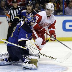 St. Louis Blues goalie Brian Elliott, left, deflects the puck as Detroit Red Wings' Jiri Hudler, of the Czech Republic, looks on during the first period of an NHL hockey game on Wednesday, April 4, 2012, in St. Louis.