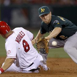 Los Angeles Angels' Kendrys Morales, left, slides before being tagged out at second trying to extend a single into a double, by Oakland Athletics shortstop Cliff Pennington during the third inning of a baseball game in Anaheim, Calif., Monday, April 16, 2012.