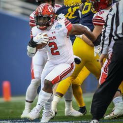 Utah Utes running back Zack Moss (2) breaks through the line on route to the first touchdown of the game at the Zaxby's Heart of Dallas Bowl between the Utah Utes and the West Virginia Mountaineers in Dallas Texas on Tuesday, Dec. 26, 2017.