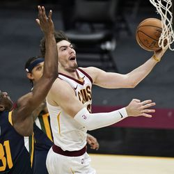 Cleveland Cavaliers' Cedi Osman, right, drives to the basket against Utah Jazz's Miye Oni, left, in the second half of an NBA basketball game, Tuesday, Jan. 12, 2021, in Cleveland.