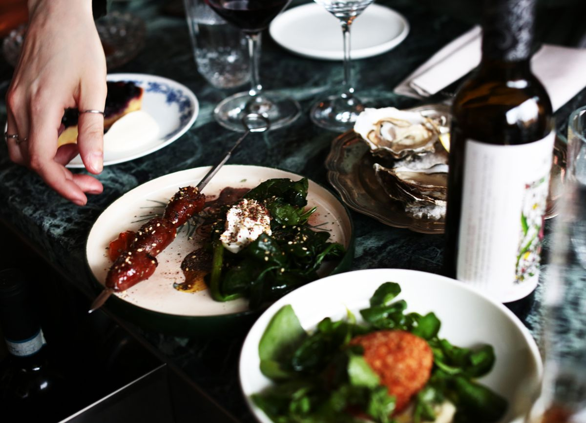 A server places a plate of meat skewer yogurty greens on a dark marble table beside a salad, an oyster plate, and a bottle of wine