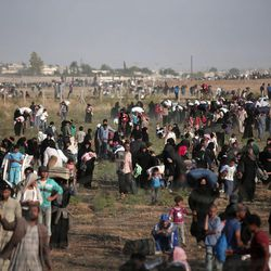 In this June 14, 2015, file photo taken from the Turkish side of the border between Turkey and Syria, in Akcakale, Sanliurfa province, southeastern Turkey, thousands of Syrian refugees walk in order to cross into Turkey. Turkey has been building a concrete wall along parts of border with Syria, trying to shut down what has long been a jihadi highway for Islamic State group fighters crossing from Turkey into Syria. According to exclusive Islamic State documents leaked to the Syrian opposition news site Zaman al-Wasl and analyzed by The Associated Press, at least 4,000 foreign IS recruits traveled through Turkey into Syria between late 2013 and most of 2014.