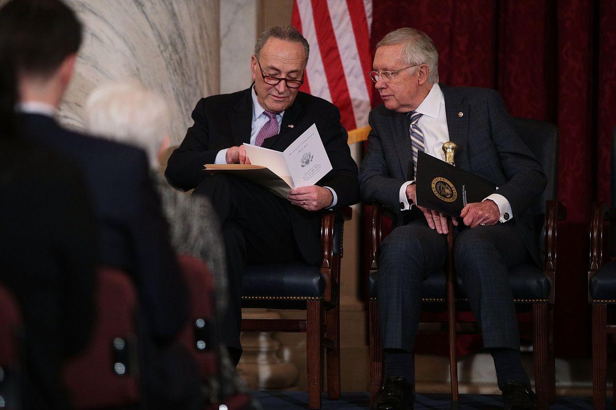 Outgoing Senate Minority Leader Harry Reid sits next to his successor, Sen. Chuck Schumer.