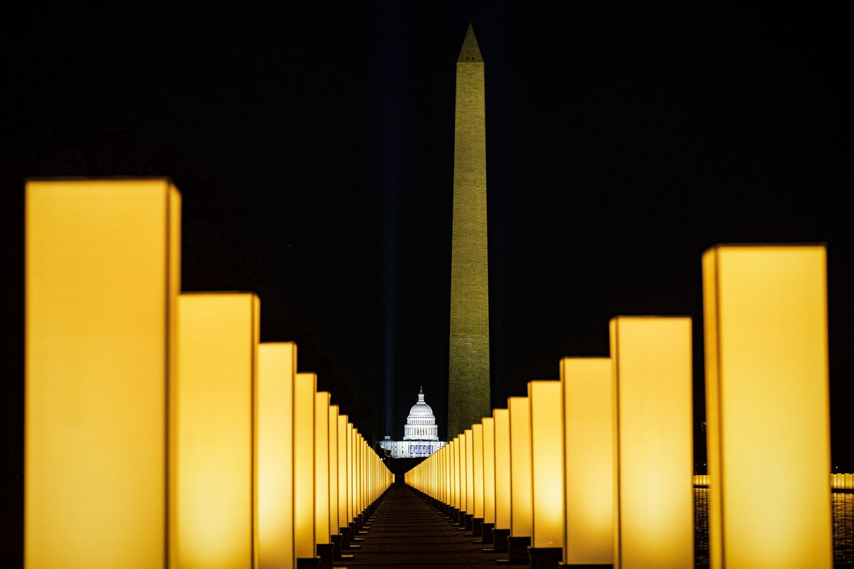 The Capitol building with the Washington Monument behind it, as seen at night through the rows of glowing tombstone-like rectangles that represent deaths from Covid-19.