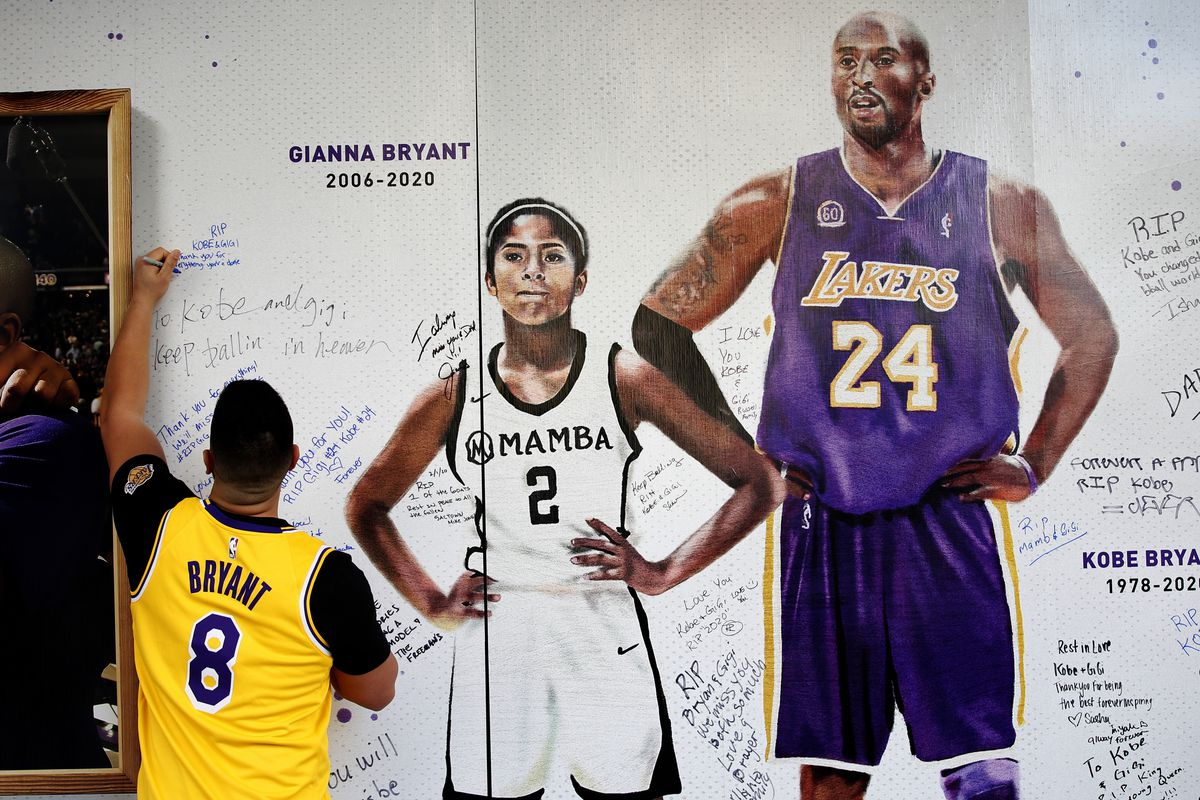 Jesse Reyes Zaragoza writes a message on a memorial display of Kobe Bryant and his daughter, Gianna in Sacramento, Calif.