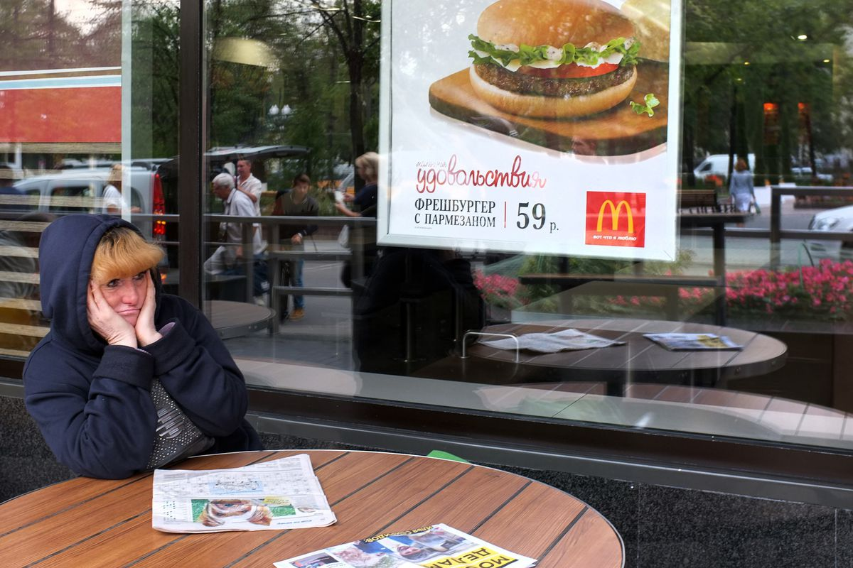A woman sits outside the Pushkin Square McDonald's after closure.