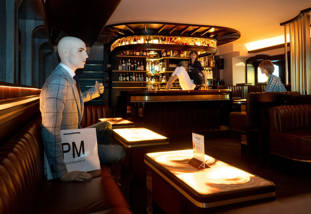 Mannequin in a suit sitting on a banquette in a bar. On the bar itself sits a female mannequin.