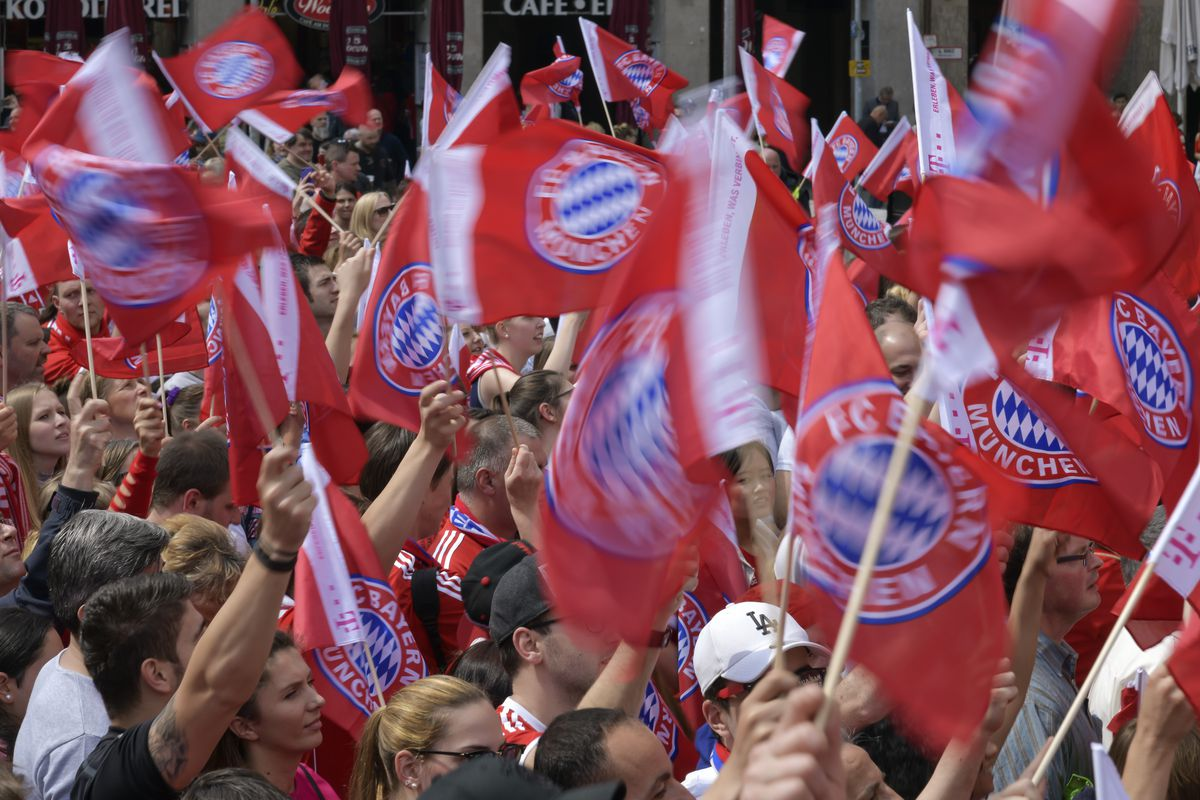 Bayern Munich's fans wave flags as players celebrate on the balcony of the city hall in Munich, southern Germany on May 20, 2018.