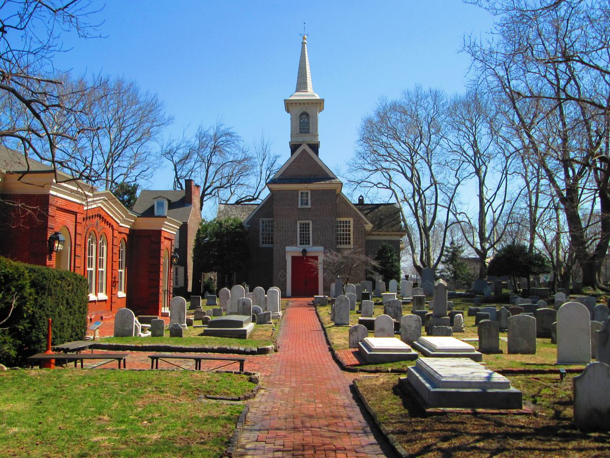 The exterior of Gloria Dei Church Historic Site in Philadelphia. The facade is grey and white. There is a red brick path and a graveyard in front of the church.