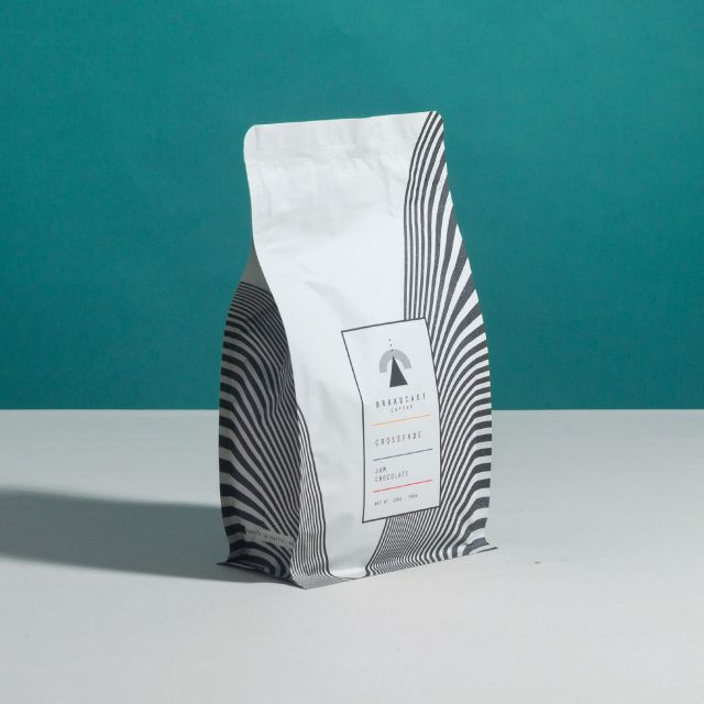 A black-and-white bag of coffee beans from Broadcast with a lined pattern; the background is bisected, with an aquamarine color on top and a gray color on the bottom