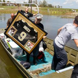 Russell Wilson unloads a water damaged Drew Brees signed shirt for his daughter Amy Keller and her husband Michael from their  Braithwaite, La. home, Saturday September 1, 2012. It was the first time the Keller family was able to get tho their flooded home since Hurricane Isaac storm surge inundated the area.