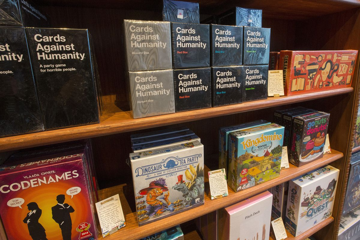 A close up of the shelf in the gift shop with the Cards Against Humanity product. Also shown is Secret Hitler, Dinosaur Tea Party, and the award-winning Kingdomino.