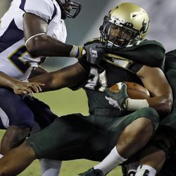 Chattanooga linebacker Wes Dothard (25) grabs South Florida running back Demetris Murray (21) by the jersey on a fourth-quarter run during an NCAA college football game Saturday, Sept. 1, 2012, in Tampa, Fla.