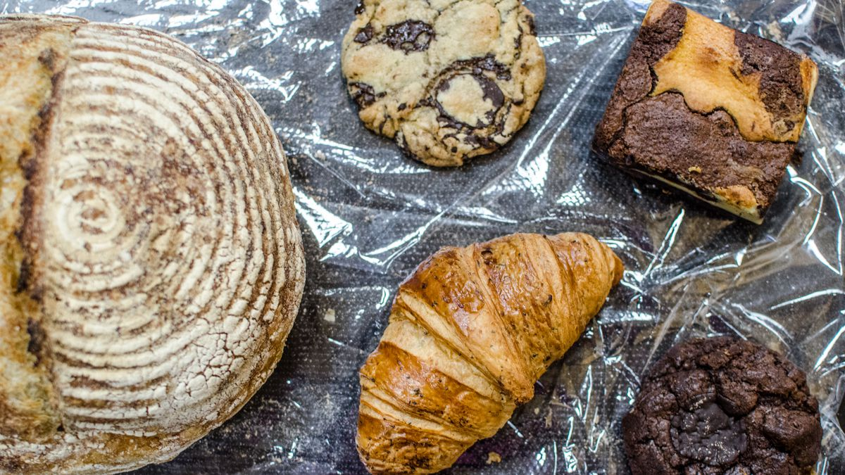 Overhead view of a round loaf of bread, a chocolate chip cookie, a croissant, a marble brownie, and a fudge cookie on a piece of plastic on a dark table