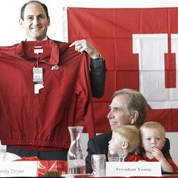Following the Board of Trustees of the University of Utah vote to accept the invitation into the Pac-10, Commissioner of the Pac-10 Athletic Conference Larry Scott is invited to be a Ute for a day by University of Utah President Michael Young (bottom right) who is holding his grandchildren Bryce and Trevor at the Rice Eccles Stadium on the campus of the University of Utah in Salt Lake City, Utah on Thursday.