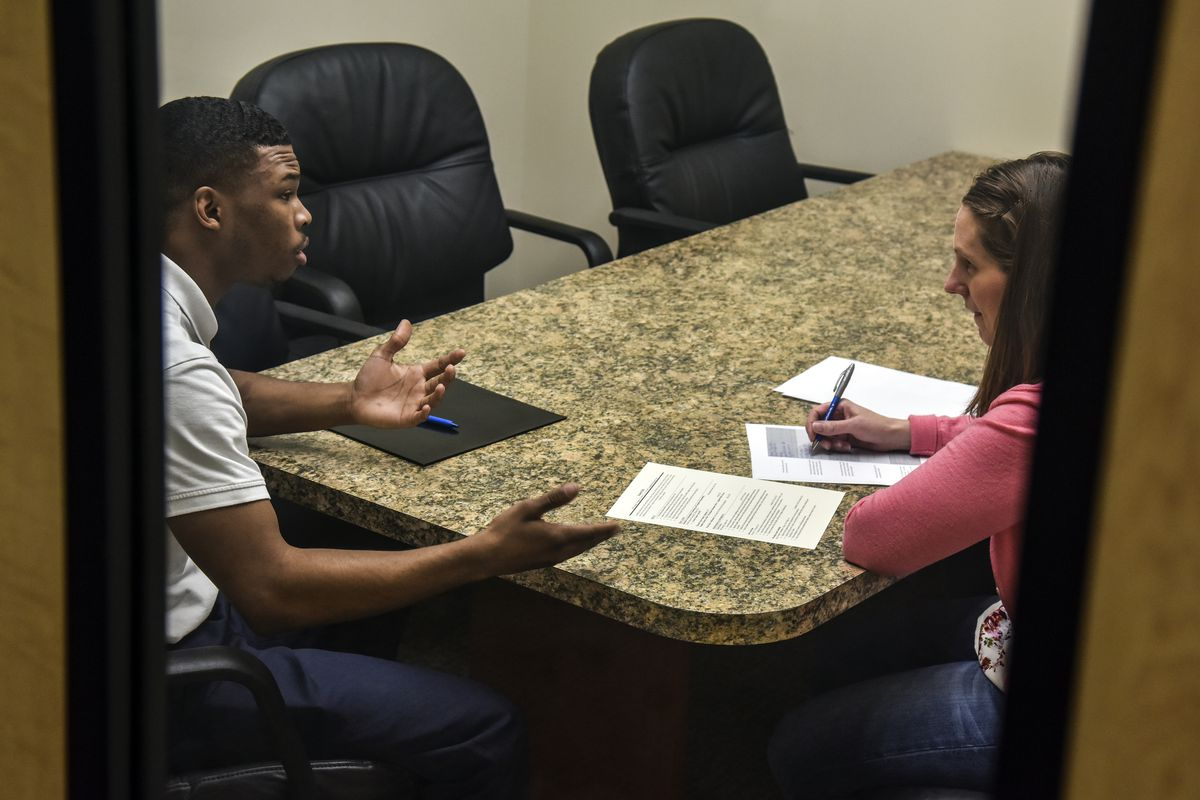 A business manager interviews a young man in a conference room for a public relations job.