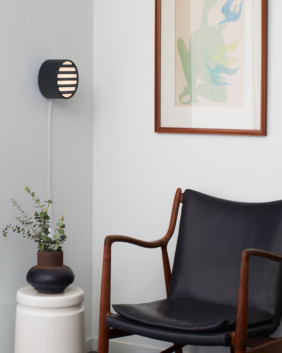 Round black sconce hanging on wall.