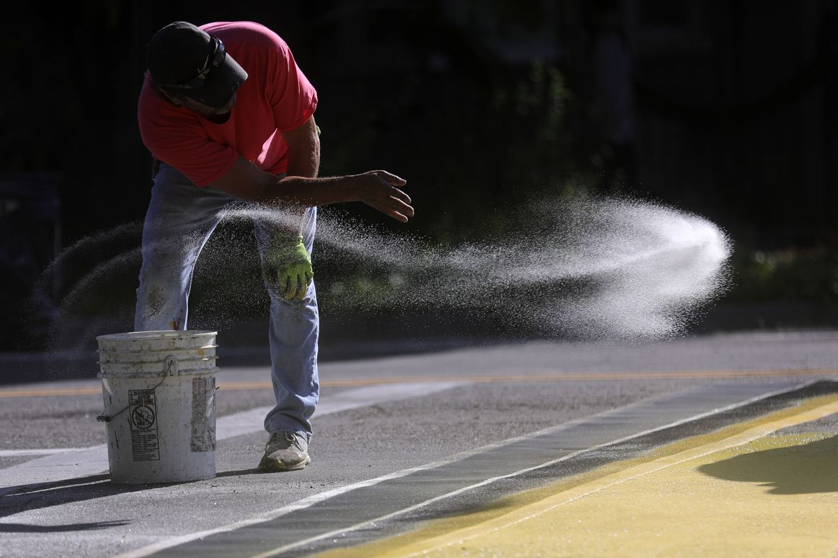 Mark Manzanares, a crew member with Peck Striping, throws reflective beading on a newly painted crosswalk at the intersection of 300 East and 700 South in Salt Lake City on Wednesday, Sept. 4, 2019. The Salt Lake City Mayor's Office, Spin and Bike Utah are partnering to turn the intersection into a multimodal community space.
