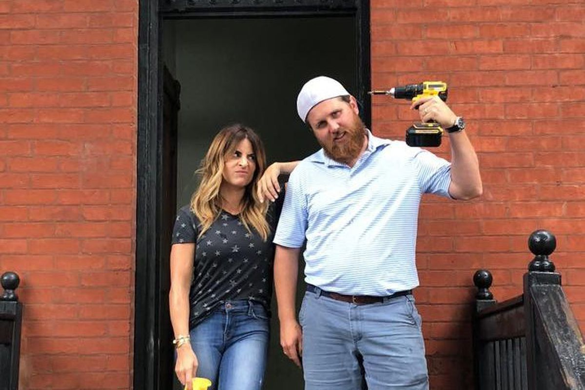 """Donovan Eckhardt and Alison Victoria, the hosts of the TV show """"Windy City Rehab,"""" are standing outside a city building and Eckhardt is holding a power drill."""