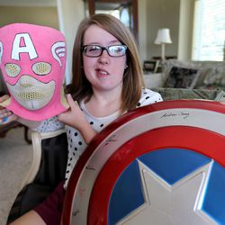 Provo resident Natalie Wright was the first adolescent to complete proton radiation therapy at San Diego at Rady Childrens Hospital at Scripps Proton Therapy Center, to treat her brain tumor, doctors made her a superhero mask to hold her head still and signed a Captain America shield for her, Monday, July 21, 2014, in Provo.