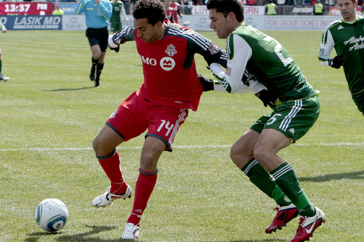 TORONTO, CANADA - MARCH 26:  Dwayne De Rosario #14 of Toronto FC battles for the ball with Steve Purdy of Portland Timbers during MLS action at BMO Field March 26, 2011 in Toronto, Ontario, Canada. (Photo by Abelimages/Getty Images)