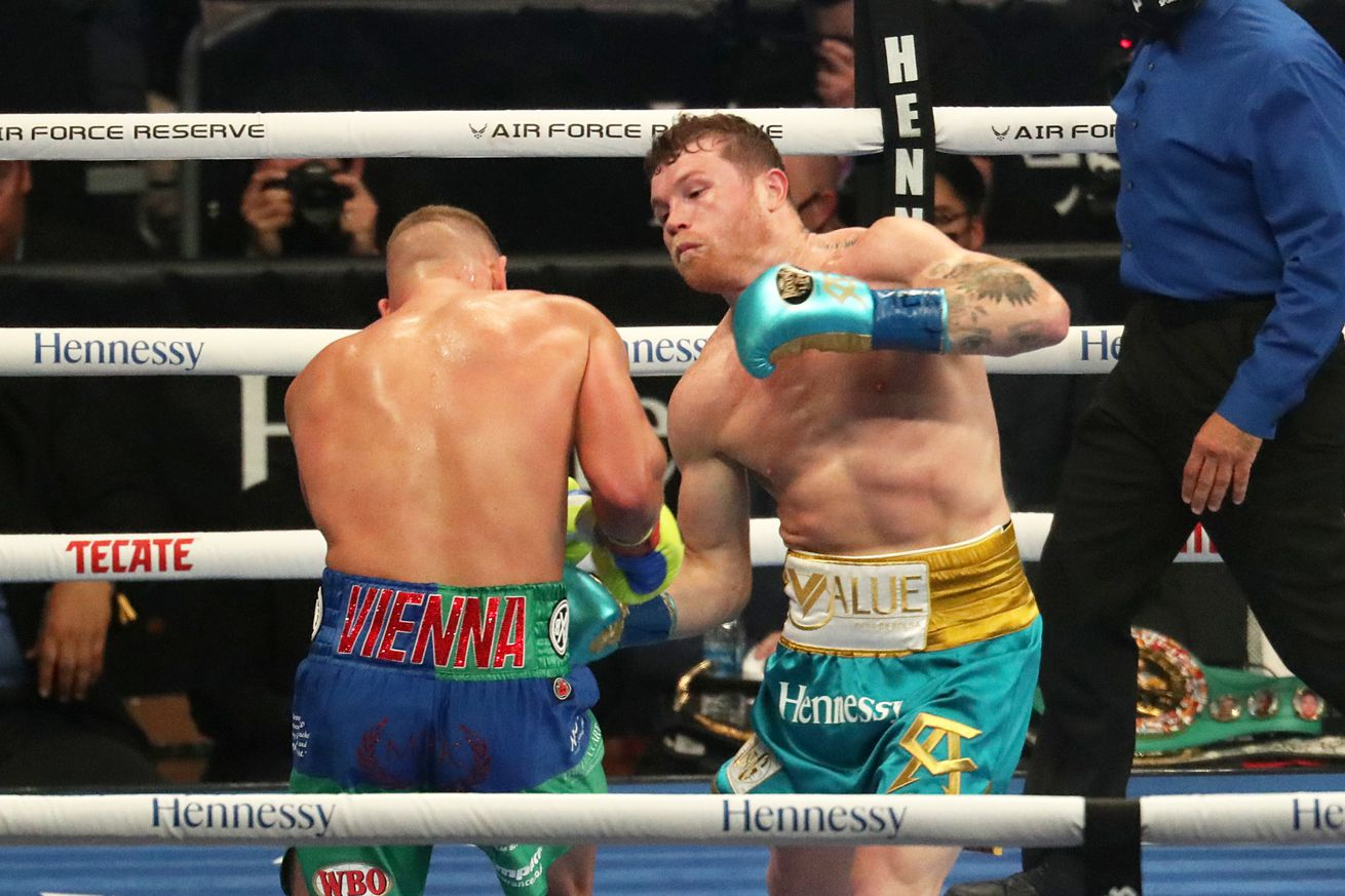 Canelo Alvarez punches Billy Joe Saunders during their fight at the AT&T Stadium