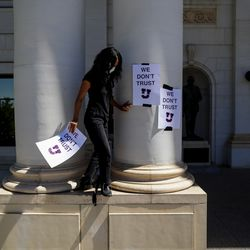 Hannah Kim places signs on the front of the Park Building at the University of Utah in Salt Lake City during a protest on Thursday, Sept. 3, 2020. Responding to the university's handling of the case of slain student Lauren McCluskey, protesters called for the resignation of university president Ruth Watkins, the abolition of the university police department, and a redistribution of police funding into counseling and social services.
