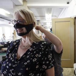 Chris LaZich, of Fleet Science Center, tries on a mask with a window with the help of Delpha Hanson, rear, in San Diego.