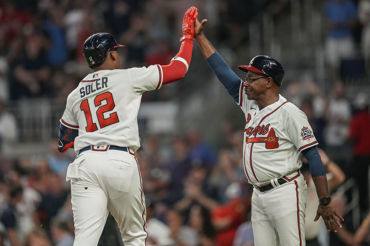 Atlanta Braves right fielder Jorge Soler (12) reacts with third base coach Ron Washington (37) after hitting a lead off home run against the Philadelphia Phillies during the first inning at Truist Park