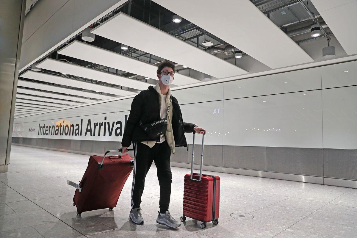 A passenger wears a mask, wheeling his luggage through Heathrow International Airport in London.