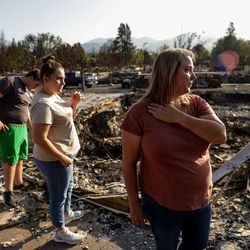 Misty Pantle, right, makes the first visit to the burned remnants of the home she shared with her children Tatum, 16, left, Tanner, 15, second from left, and Reese and her sister, Tammy Johnson, both not pictured, in Talent, Ore., on Saturday, Sept. 19, 2020. Their home was one of more than 2,300 residences destroyed when the Almeda Fire swept through the towns of Talent and Phoenix in southern Oregon.