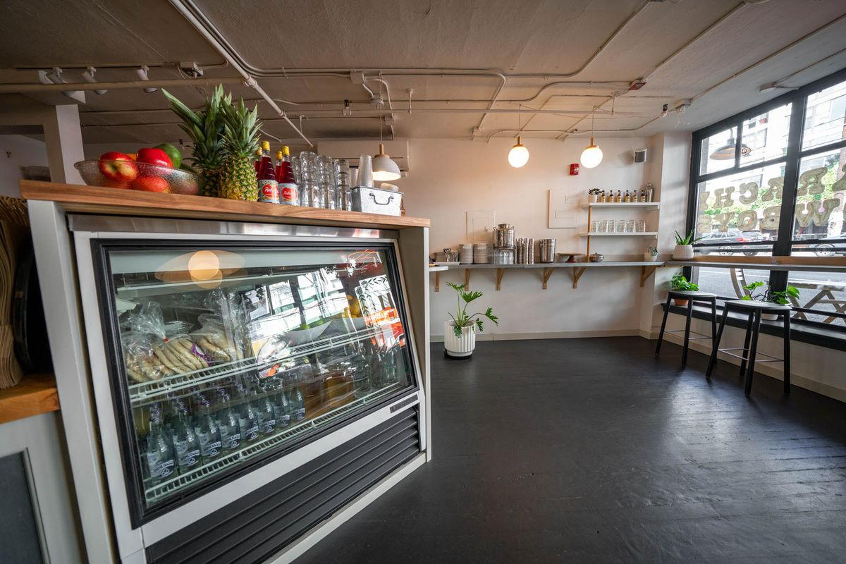 The space at Karachi Cowboys features a retail case with fruit sitting on top (including a pineapple), and a large window with stools looking out onto the street.