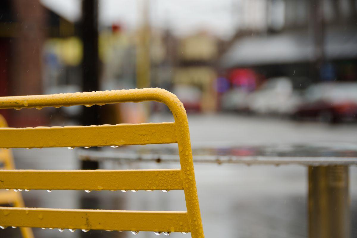 A rain-soaked yellow bench.