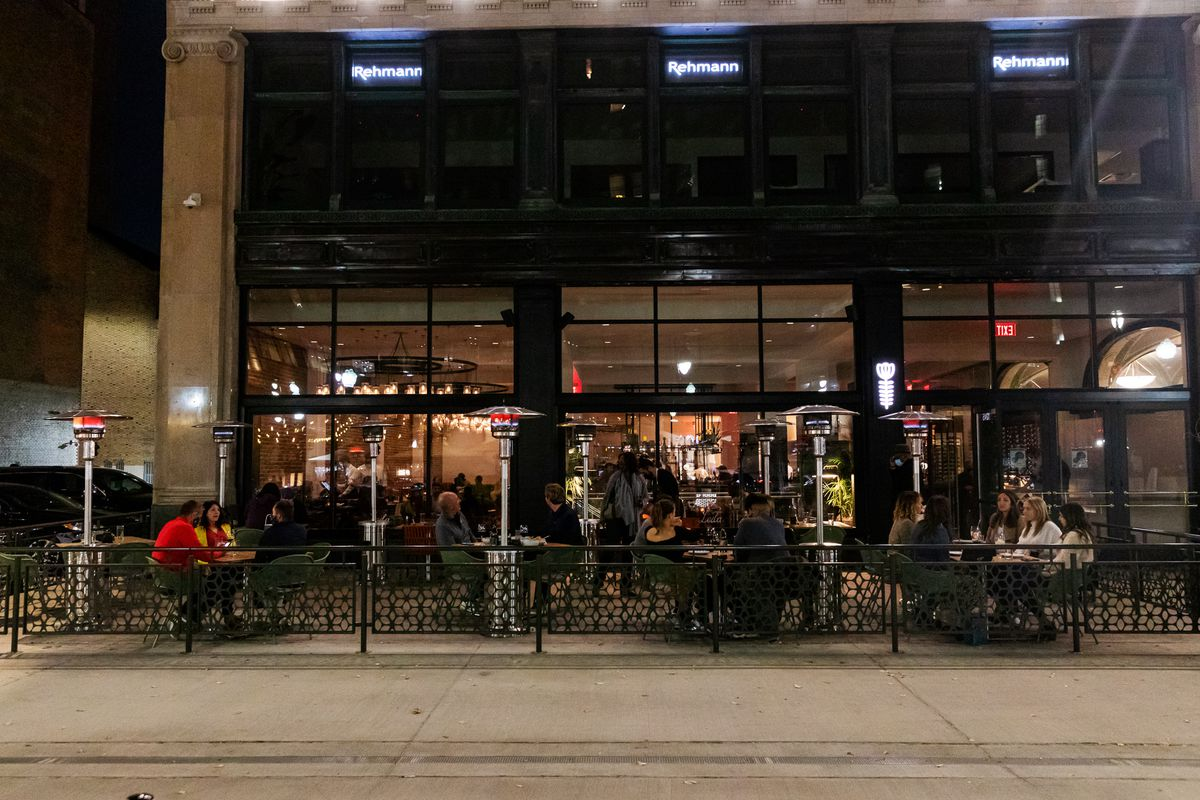 Customers sit out on the patio surrounded by heaters at night.
