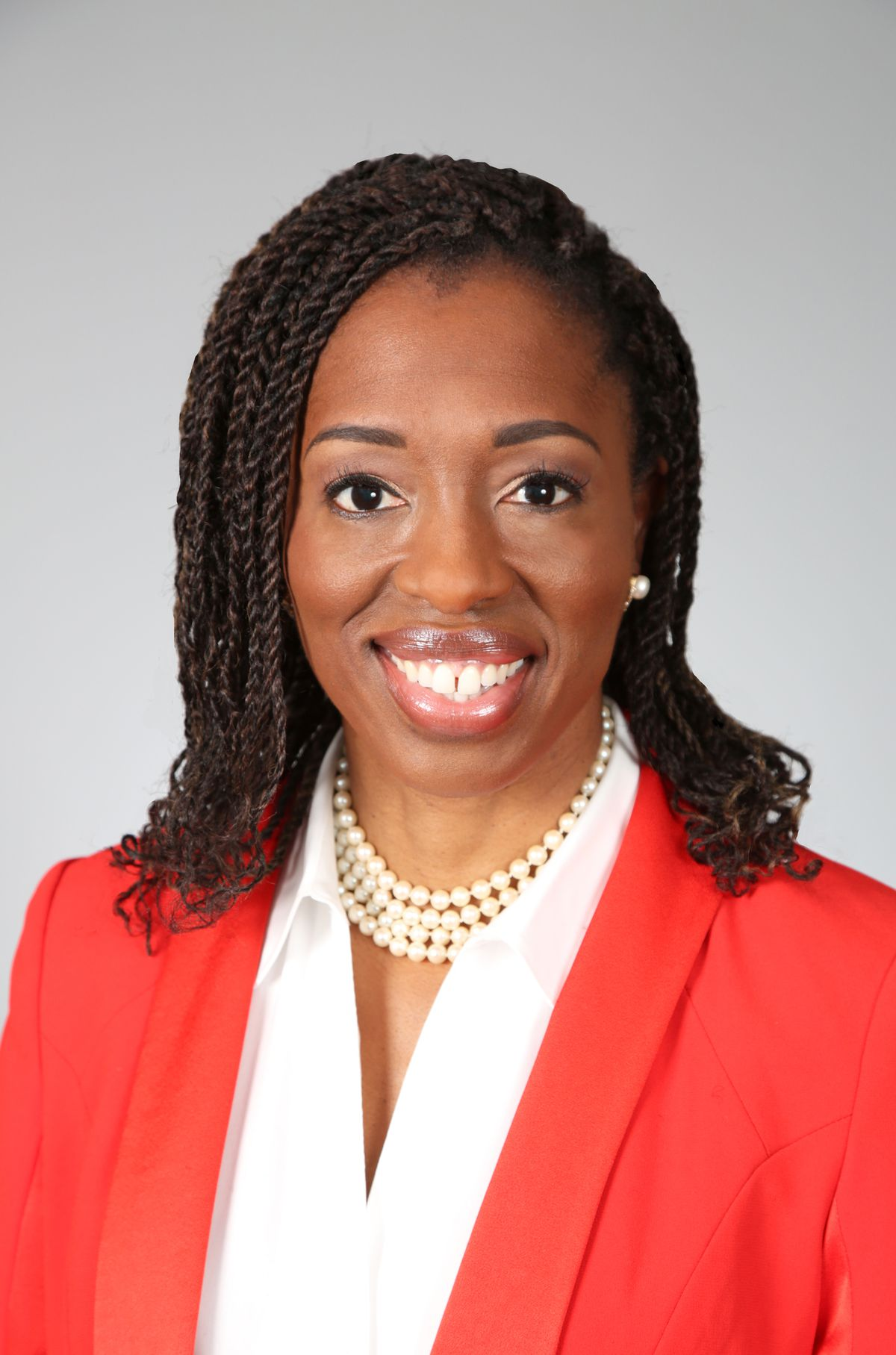 Dr. Ngozi Ezike poses in front of a white background. She is wearing a bright red blazer, with a white shirt and a pearl necklace.