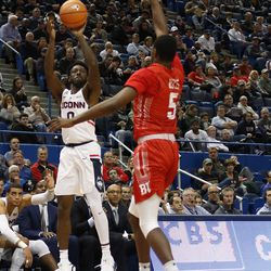 UConn's Antwoine Anderson (0) attempts a three-pointer in front of his bench over an oncoming Boston University defender.