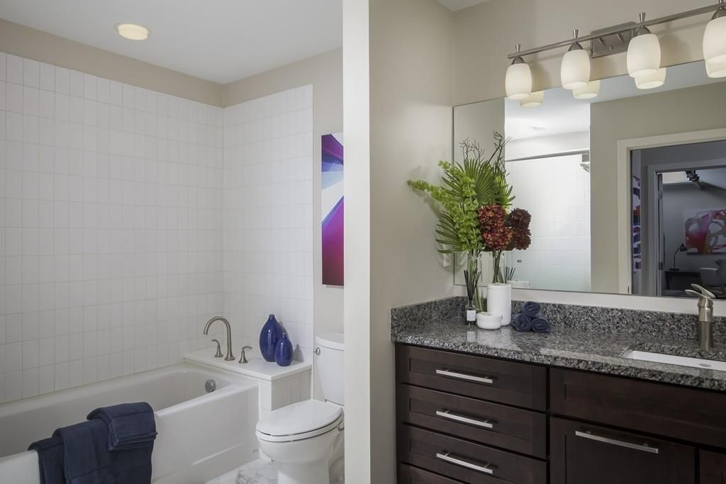 A bathroom with a vanity and a shower with no curtain.