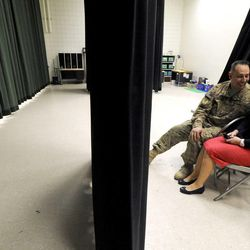 Air Force Tech Sgt. Edward Goettig spends a moment with his wife, Tracie, on the stage while waiting to surprise his two daughters Addie and Olivia at Fox Hollow Elementary School on Thursday, March 6, 2014. Goettig had been deployed to Afghanistan since Aug. 27, 2013.