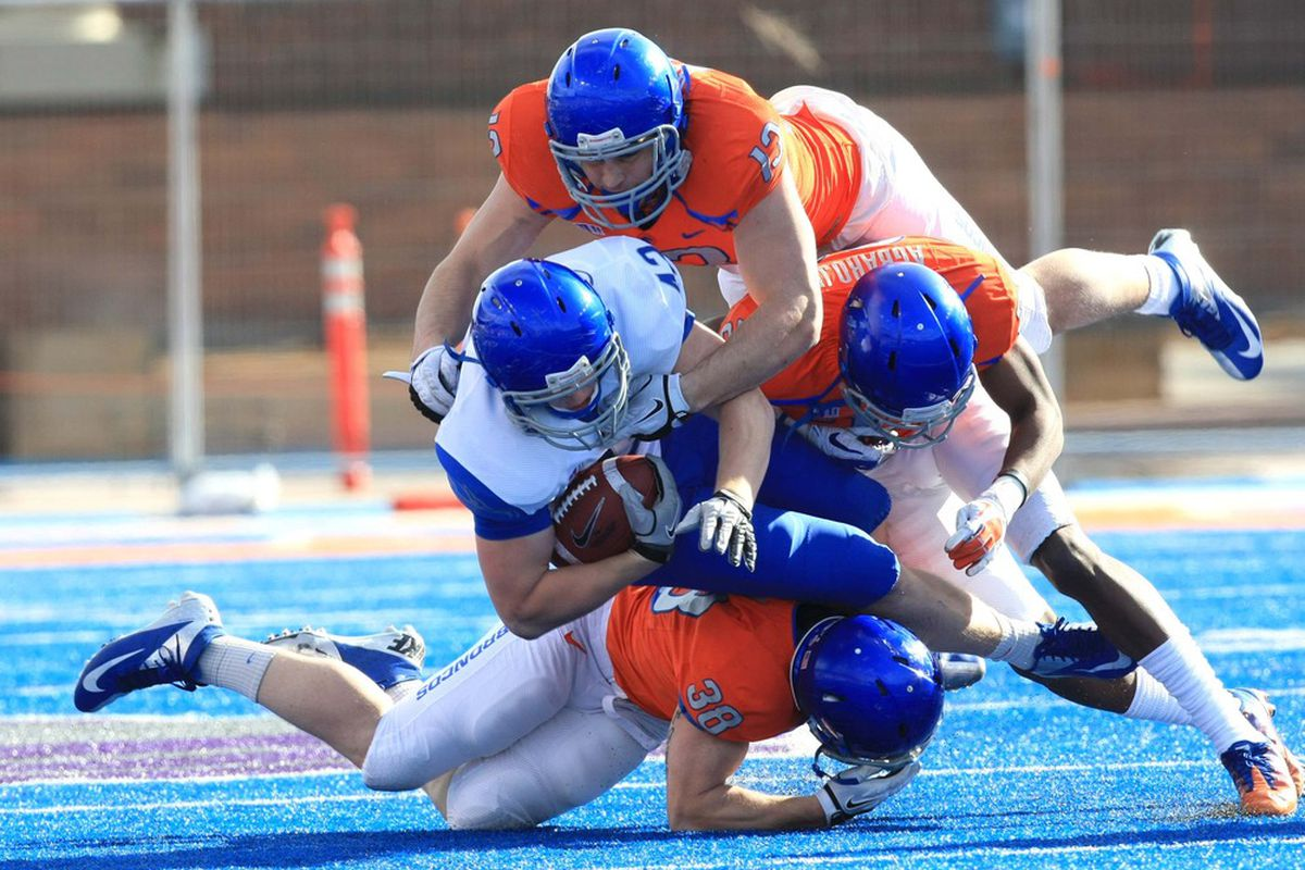 April 16, 2012; Boise, ID, USA; Boise  Broncos tight end Jake Hardee (42) is tackled by linebackers  Renaud, (13), Eric Agbaroji (23) and Corey Bell (38)  during the spring game at Bronco Stadium.  Mandatory Credit: Brian Losness-US PRESSWIRE