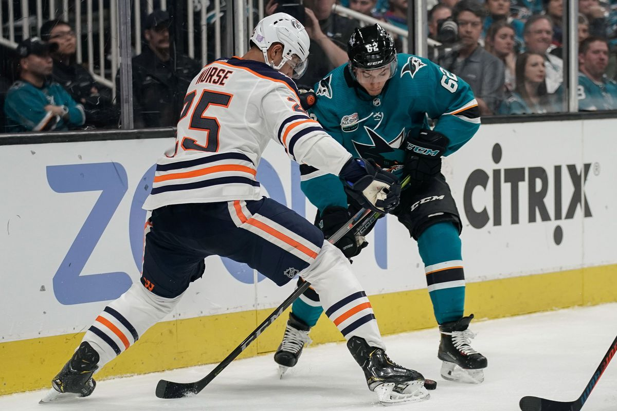 Nov 20, 2018; San Jose, CA, USA; Edmonton Oilers defenseman Darnell Nurse (25) and San Jose Sharks right wing Kevin Labanc (62) fight for control of the puck during the second period at SAP Center at San Jose. Mandatory Credit: Stan Szeto