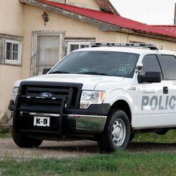 """The """"K-9"""" police truck of the Vaughn, N.M. Police Department is shown in driveway of former Vaughn Police Chief Ernest """"Chris"""" Armijo Wednesday, Sept. 26, 2012 photo. Vaughn officials announced Wednesday that Armijo resigned after news stories reported that he was not allowed to carry a gun due to his criminal record, leaving the town with just one certified member on its police- force a drug-sniffing dog named Nikka. The town's only other officer isn't certified and pleaded guilty to charges of assault and battery last year."""