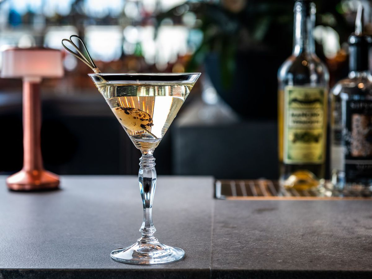 Martini-style cocktail with bar in the background
