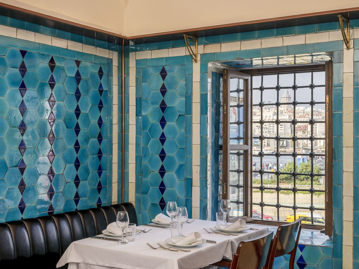 A corner table with dark leather banquet and chairs beneath bright blue tiled walls and a window looking out on Istanbul