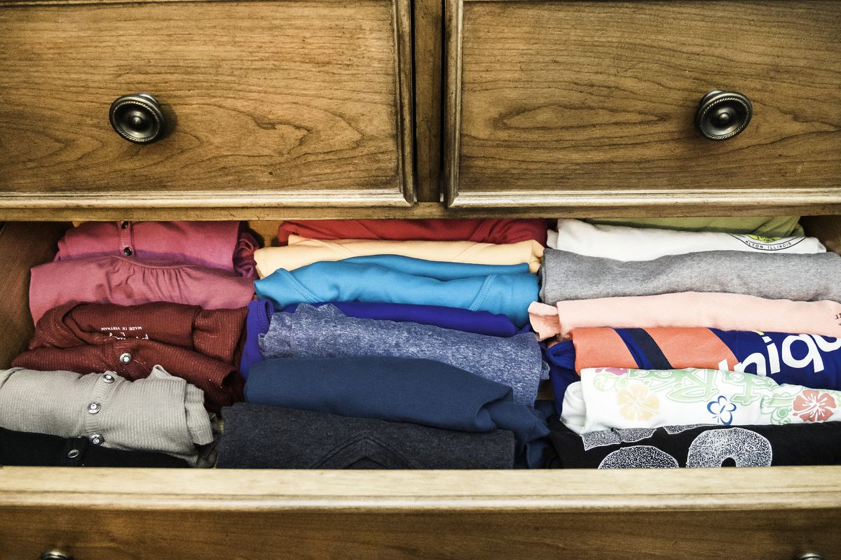 A drawer overstuffed with folded T-shirts.