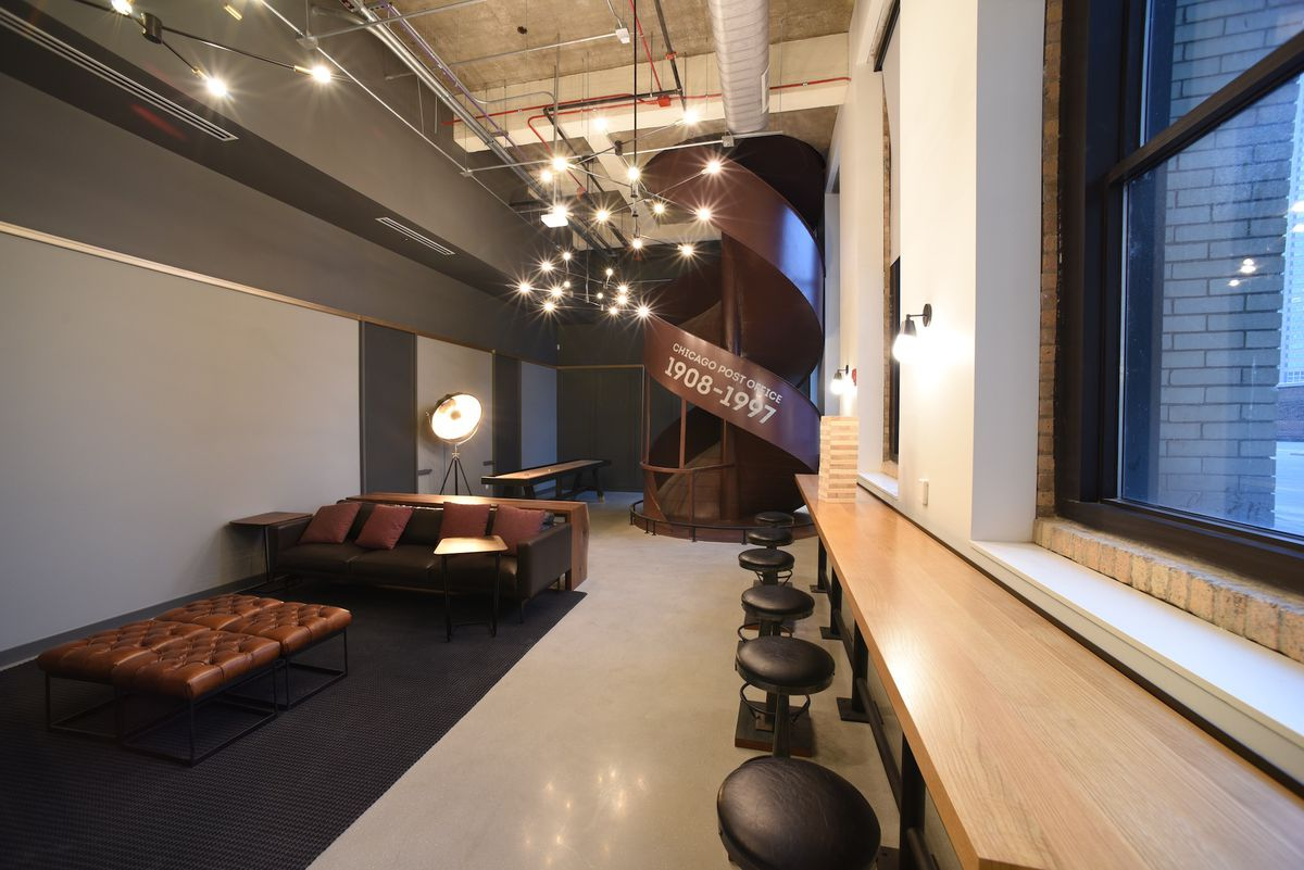An open office space with stools, sofas, and a brown metal floor-to-ceiling spiral slide.