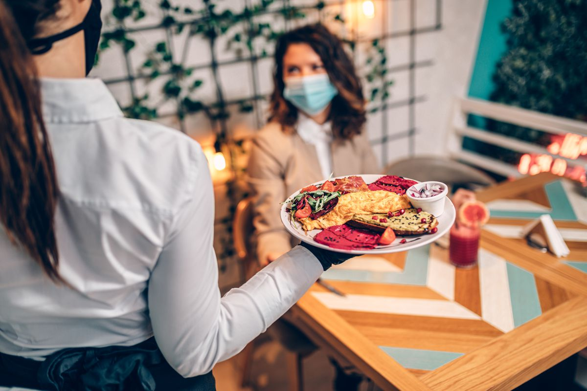 A masked waiter brings food to a masked diner sitting at a table