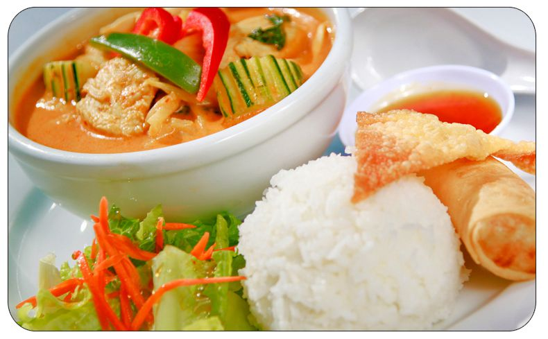 A close up image showing a bowl of chicken curry beside white rice, crispy wonton and sweet and sour sauce