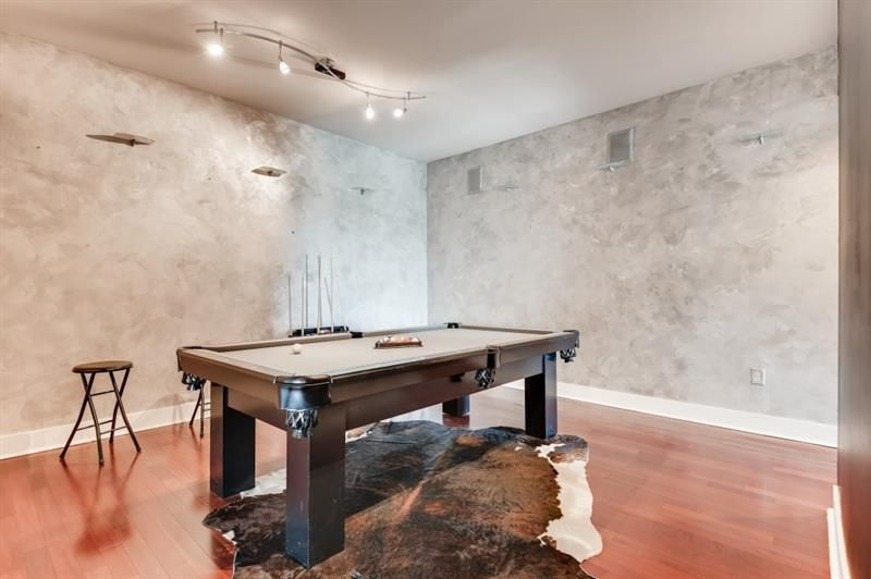 A living room space with a pool table and a cow skin rug.