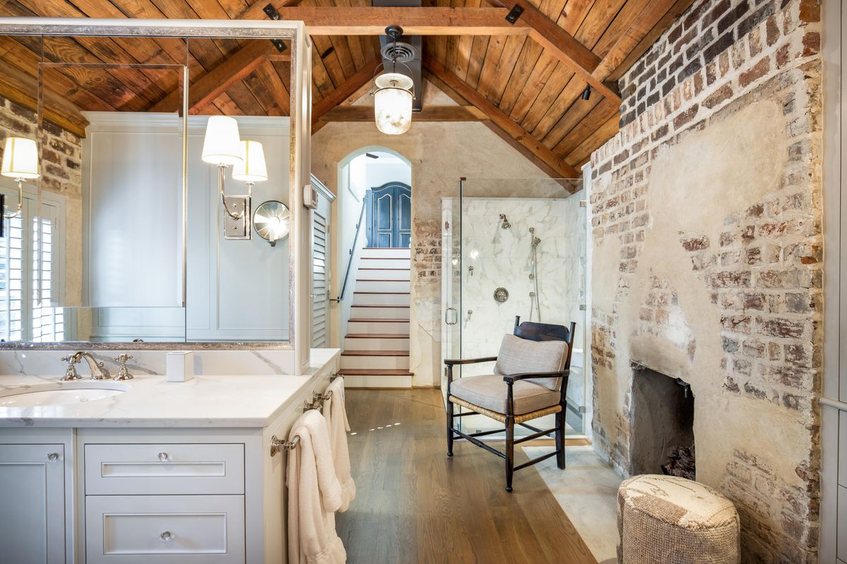 A large bathroom has exposed brick with a fireplace, and a shower and sink.